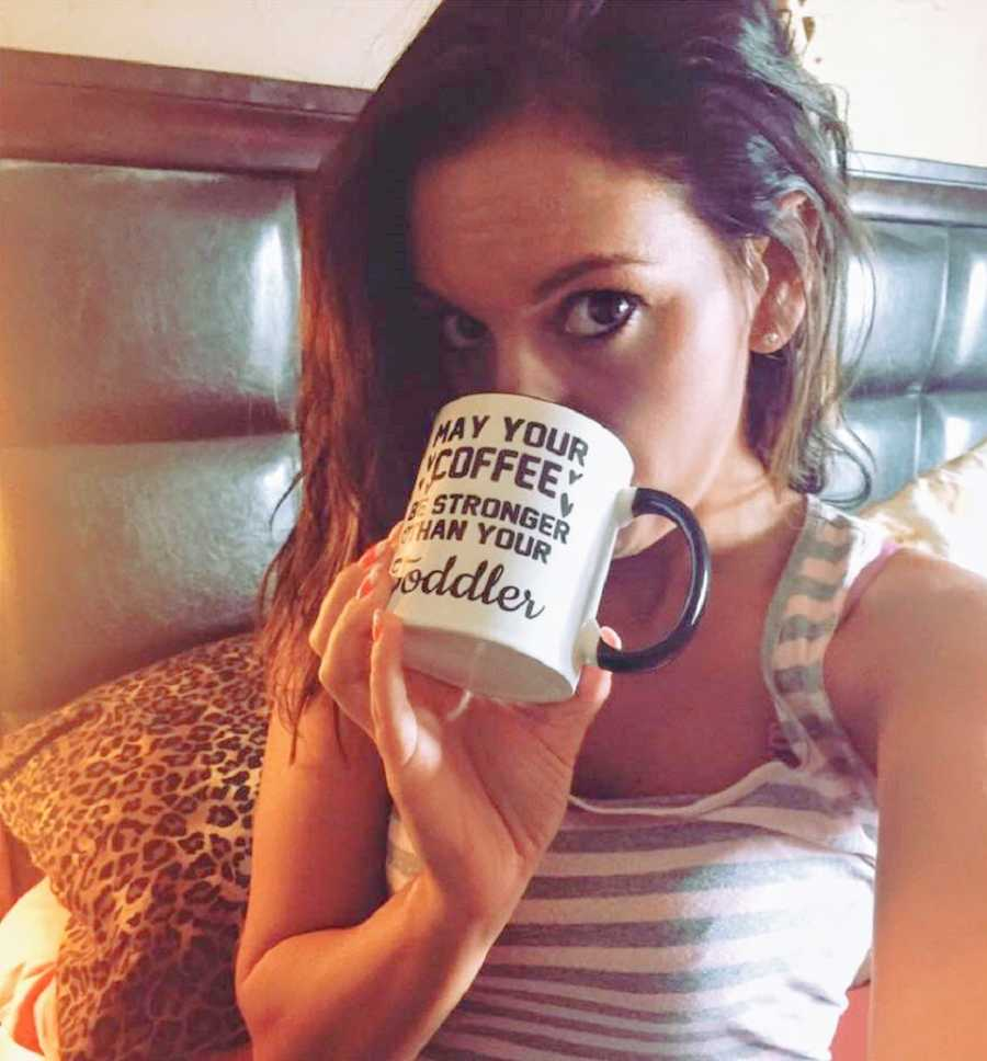 A mom drinks out of a coffee mug in bed