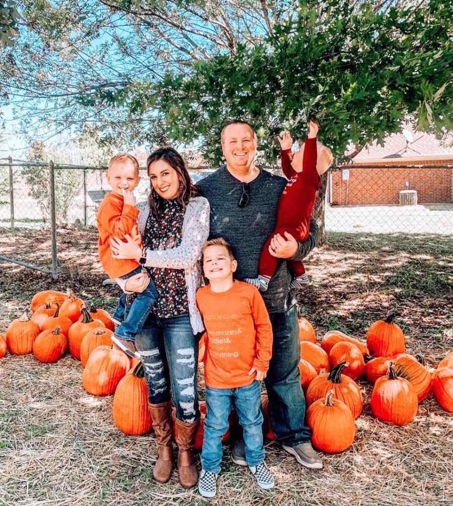 Parents hold their three children on Halloween