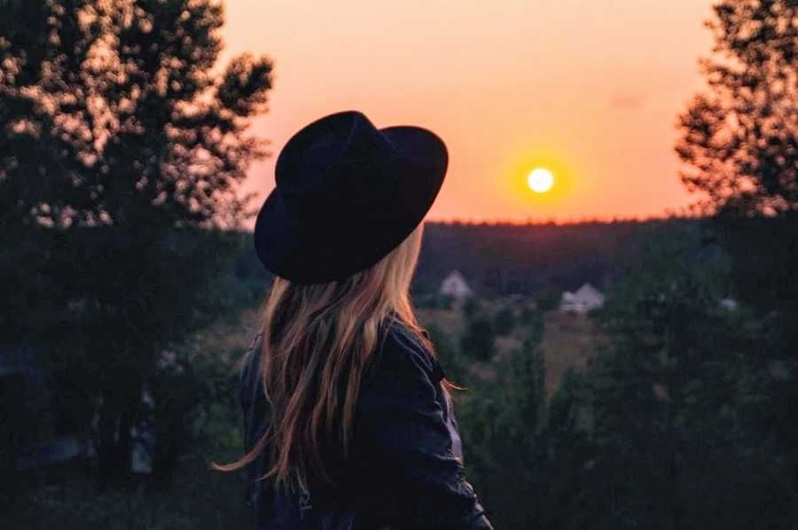 A woman in a hat looks at a sunset