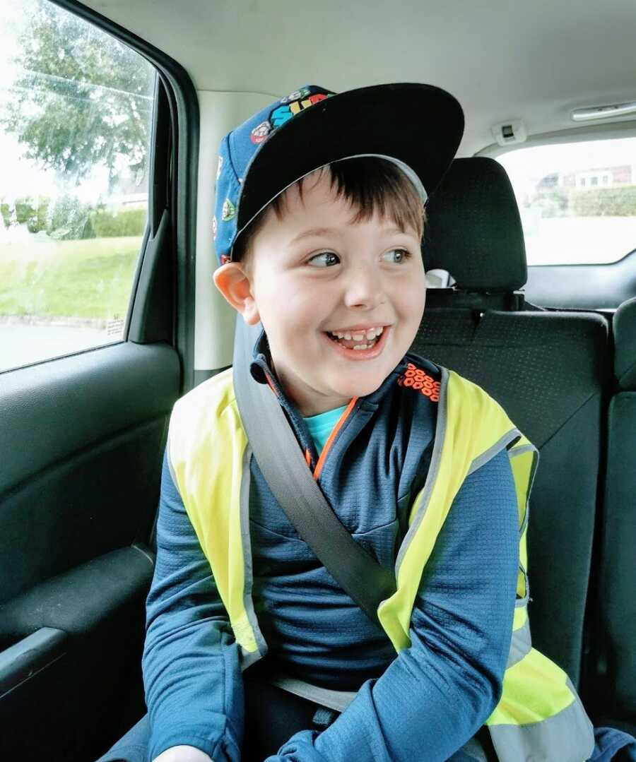 Boy sitting in car wearing hat and vest