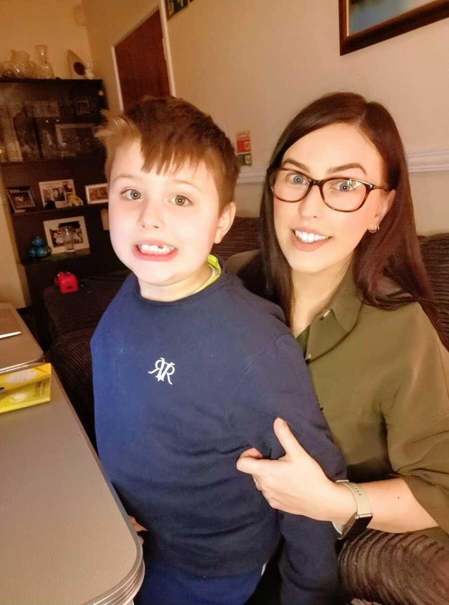 Boy in blue sweater sits on mom's lap