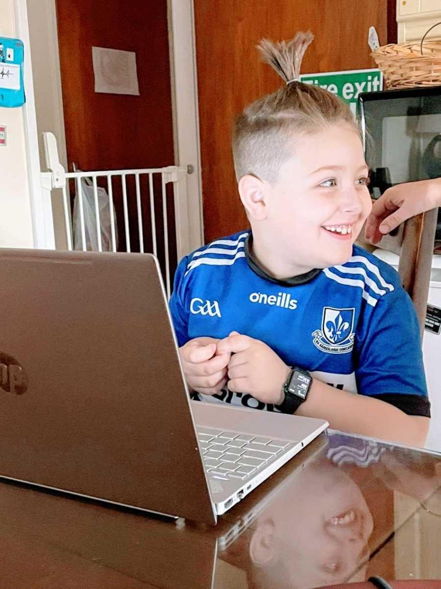 Am Autistic boy wearing a blue shirt sits at a computer
