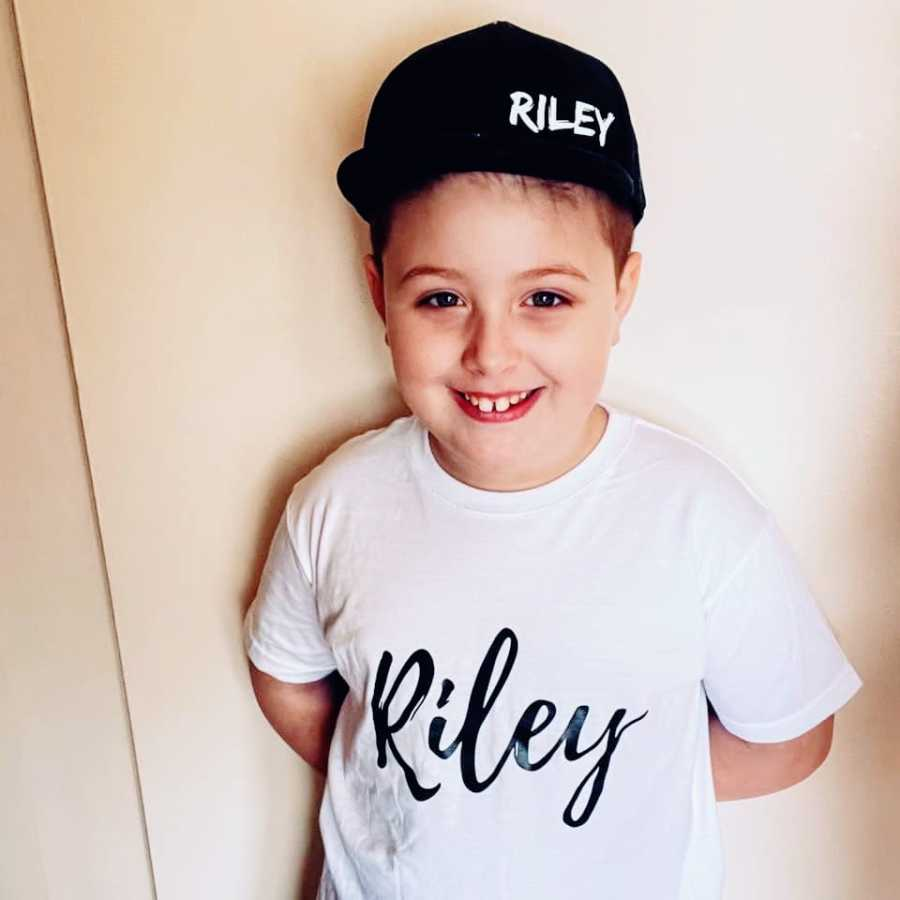A boy wearing a black hat and a white shirt with his name on them