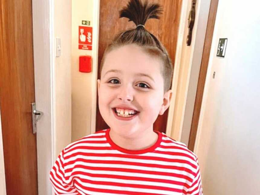 Boy with autism wearing red striped shirt