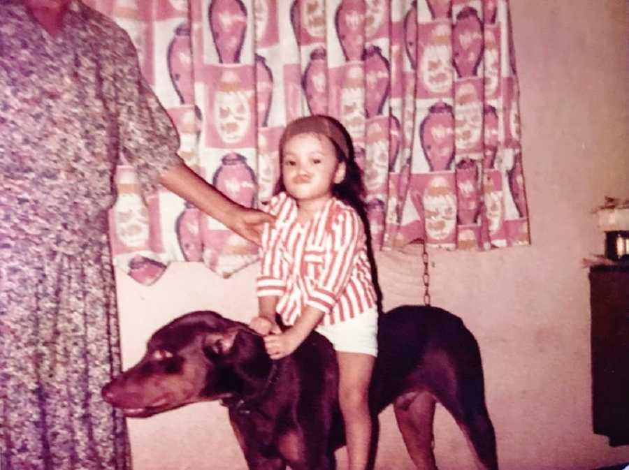 A little girl sits on a big dog like a horse