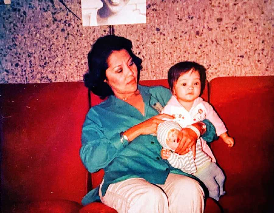 A woman holds her adoptive daughter on a couch