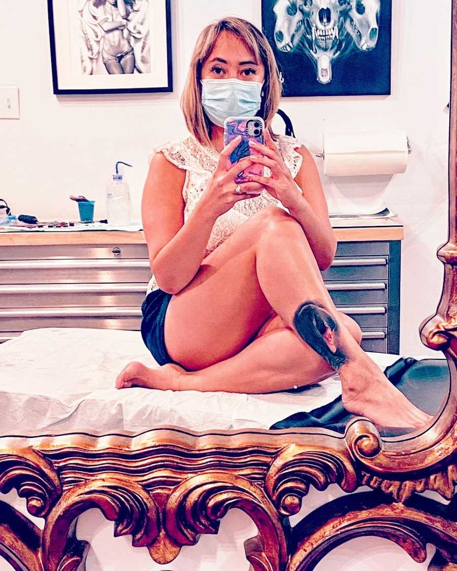 A woman sits on a bed wearing a mask with her legs crossed
