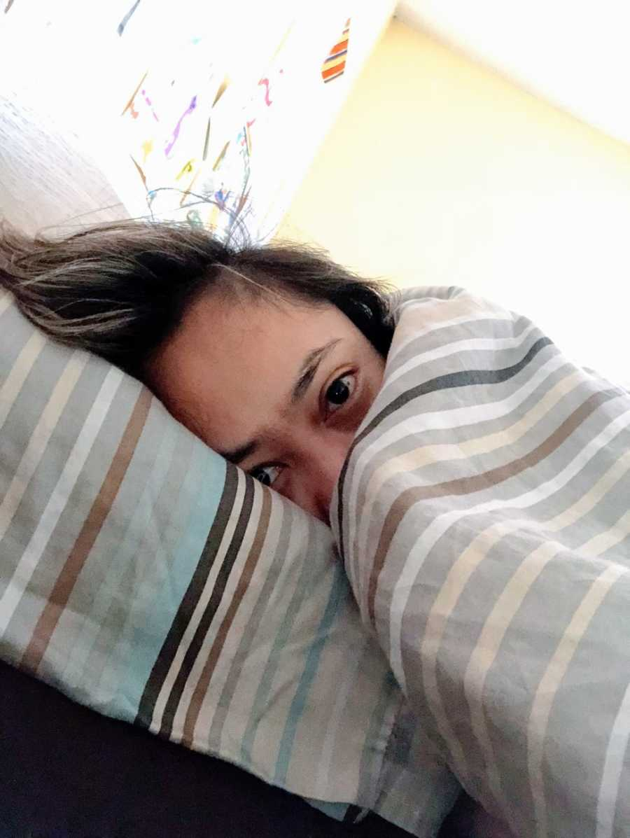 A woman lies in her bed beneath the covers