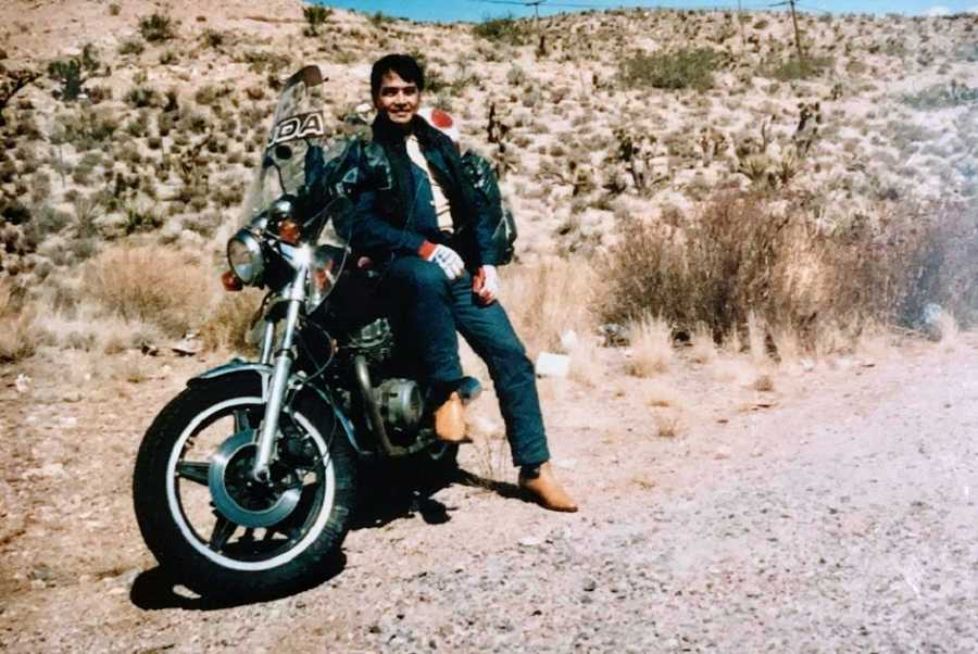 A man sits by a motorcycle out in the desert