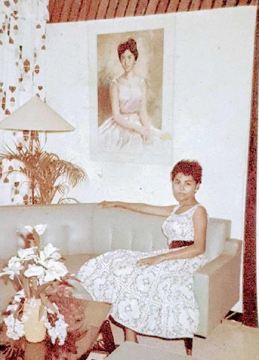 A young woman sits on a couch by herself
