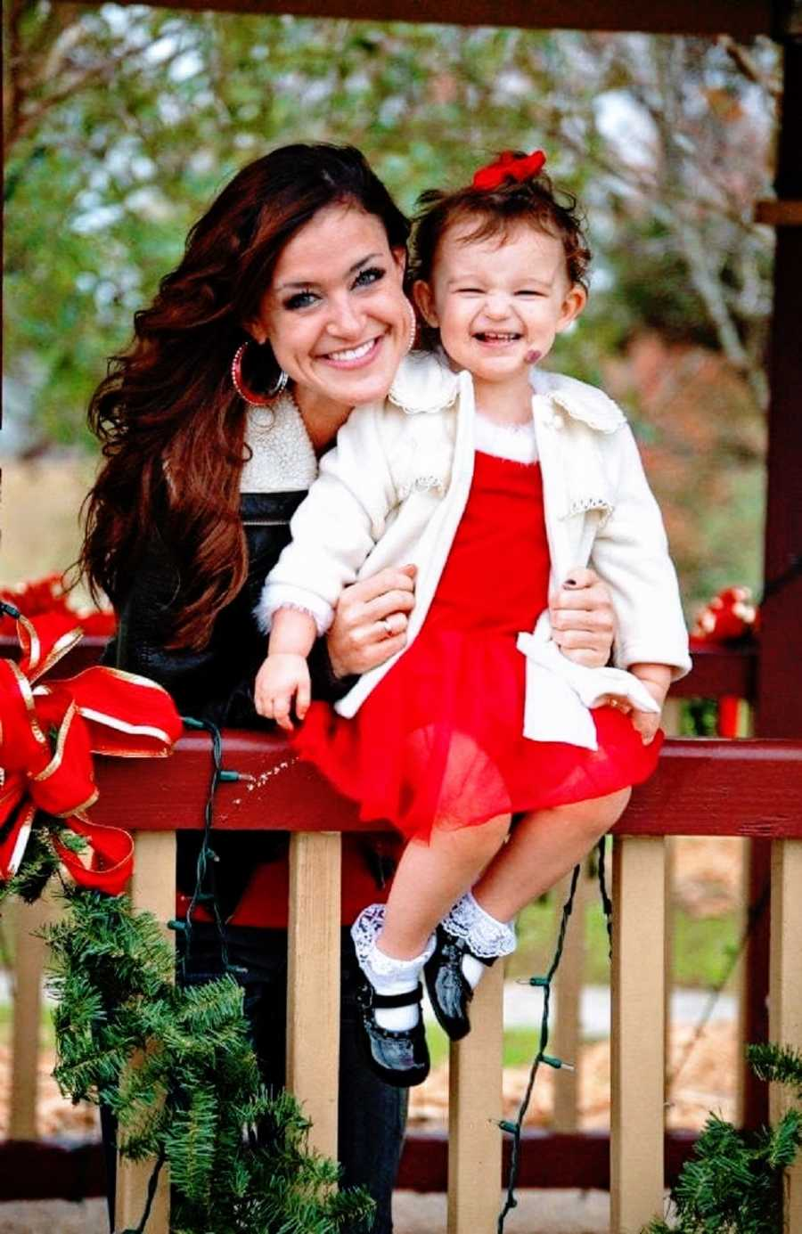 Mom holds young daughter dressed for Christmas