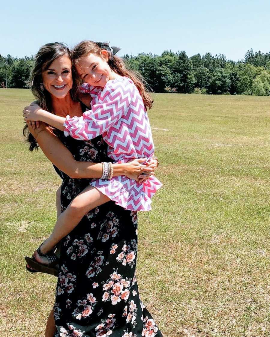 Young mother holds daughter up outside