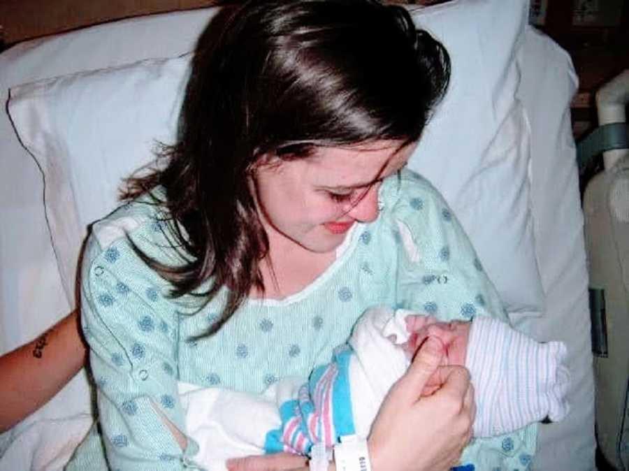 Teen mom holds newborn daughter in hospital
