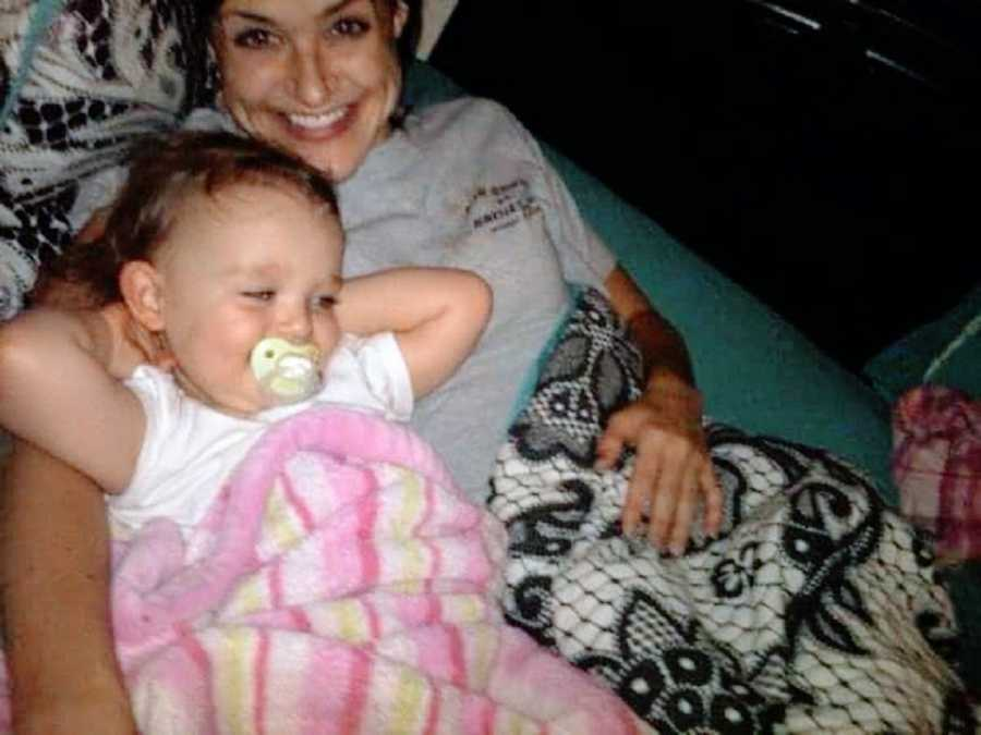 Mom and baby girl sit on couch together