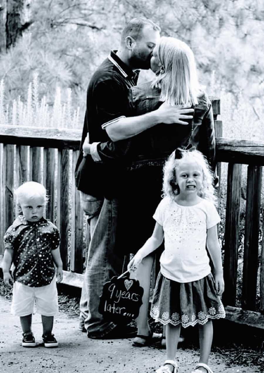 A husband and wife kiss while their two children stand nearby