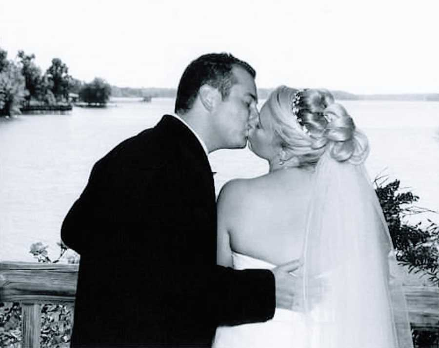 A woman and her husband kiss on their wedding anniversary