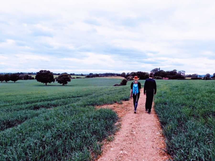 Two people walk together in a field