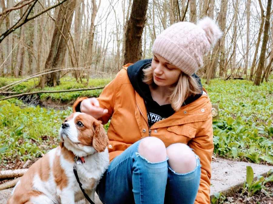 Woman sits with small dog outside