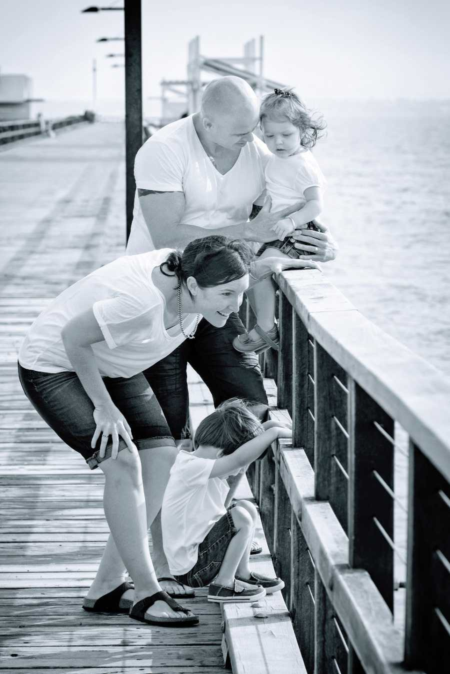Parents with their two young children on a bridge by the water