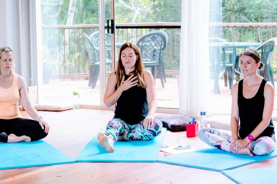 A woman sits alone on a yoga mat with her hand on her chest