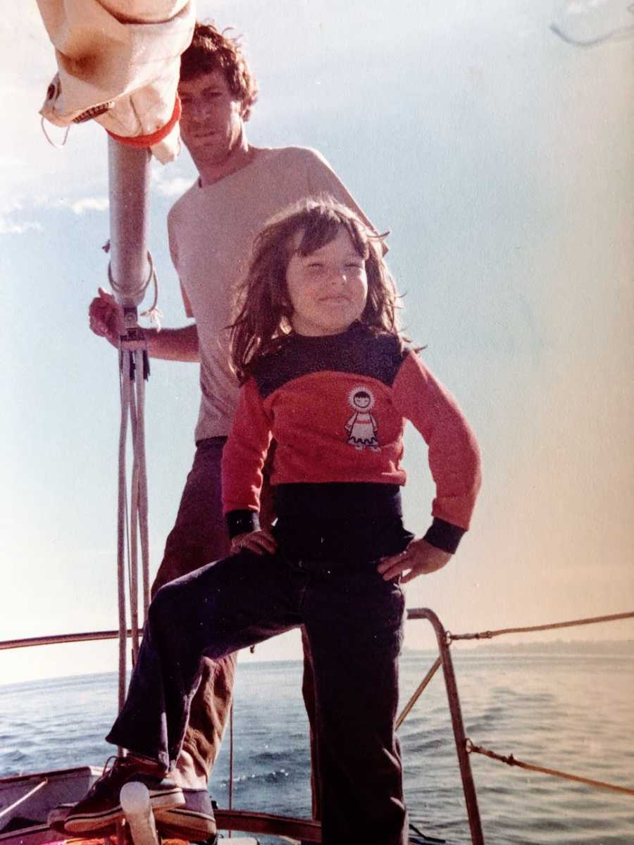 A little girl stands on a boat with her hands on her hips