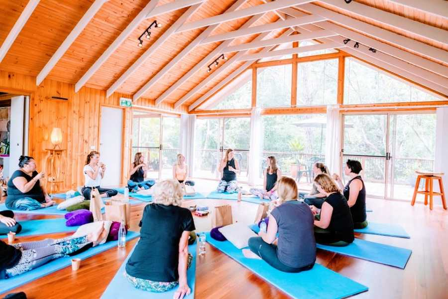 A woman sits with a class full of people on yoga mats