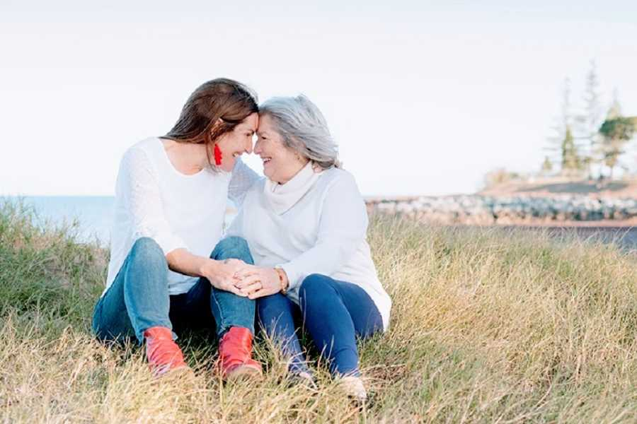A woman and her mother sit together in a grassy field