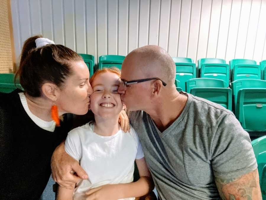Parents kiss their daughter on either cheek