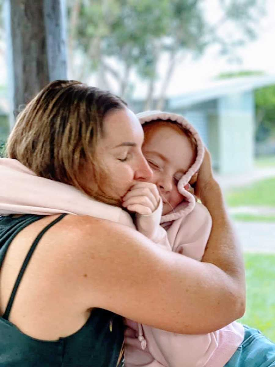 A mother hugs her daughter who is wearing a pink hoodie