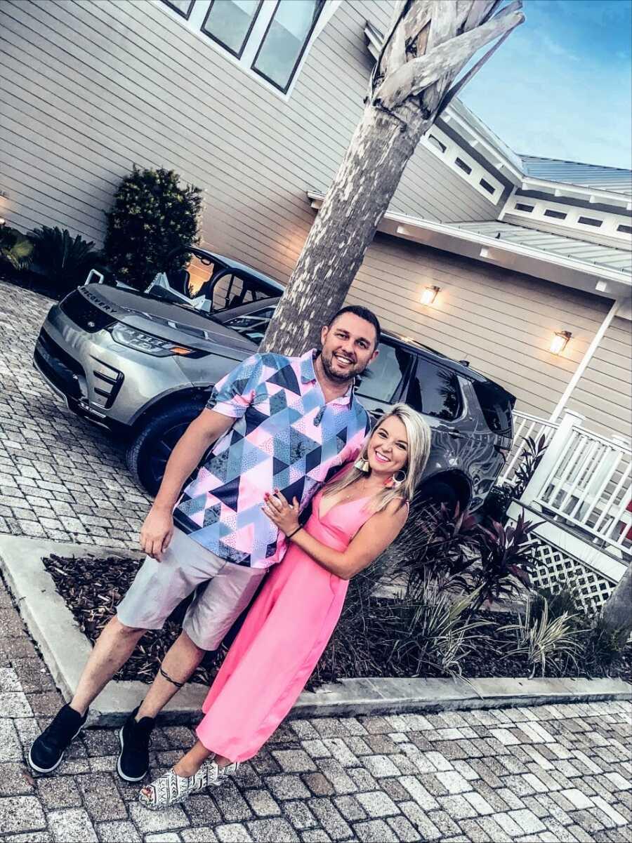 一对患有不明原因不孕不育的夫妇在约会之夜前穿着色彩搭配的衣服在他们的前院拍了张照片