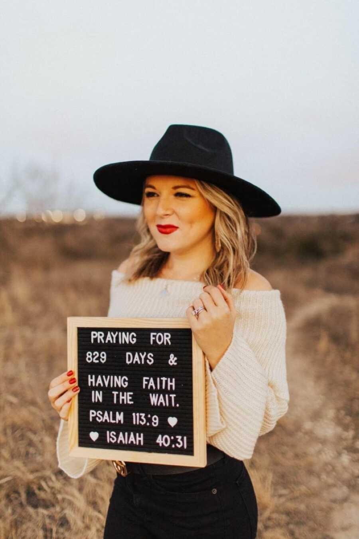 """一名与不明原因不孕作斗争的妇女身穿白色毛衣,头戴黑色帽子,挂着""""祈祷829天,相信等待""""的牌子拍照"""