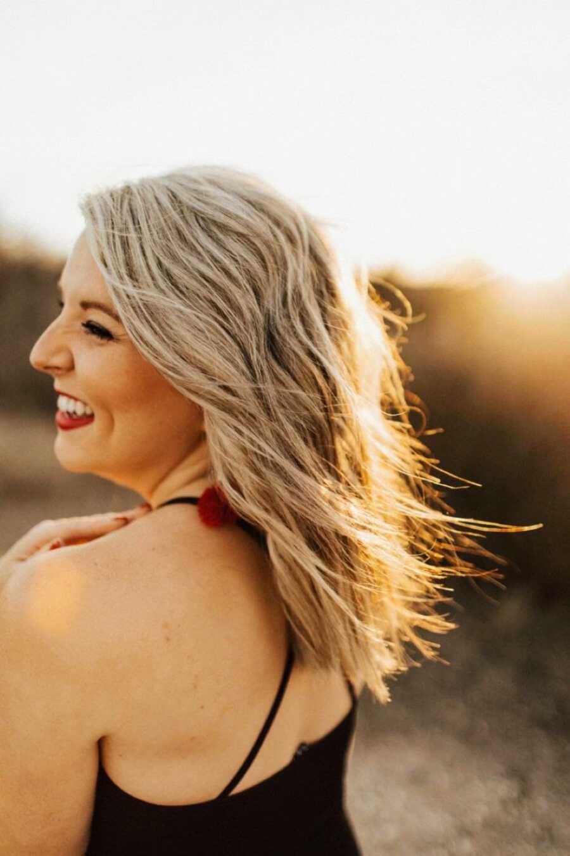 在黄金时段,一名患有不明原因的不孕症的妇女微笑着拍照,波浪状的头发随风飘动