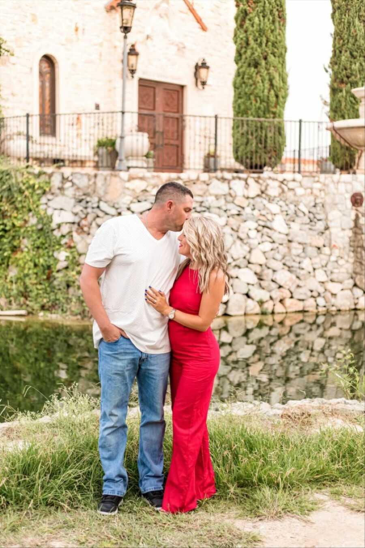 穿着一件白色的T恤和蓝色牛仔裤的男人在外面拍照时亲吻他的妻子的额头