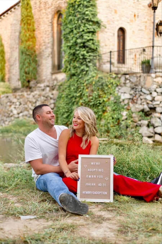 一对年轻的夫妇坐在草地上微笑着宣布他们正在收养胚胎