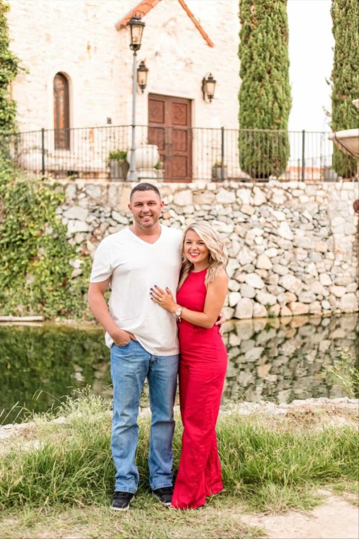 一对年轻夫妇在户外拍照时笑容满面,妻子穿着红色连体裤,丈夫穿着牛仔裤和白色t恤