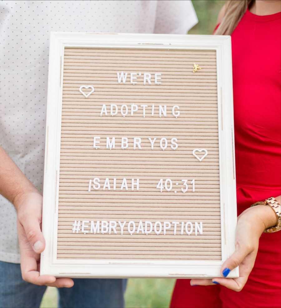 """已婚夫妇在努力努力下努力后,已婚夫妇举起标志阅读""""我们正在采用胚胎"""""""