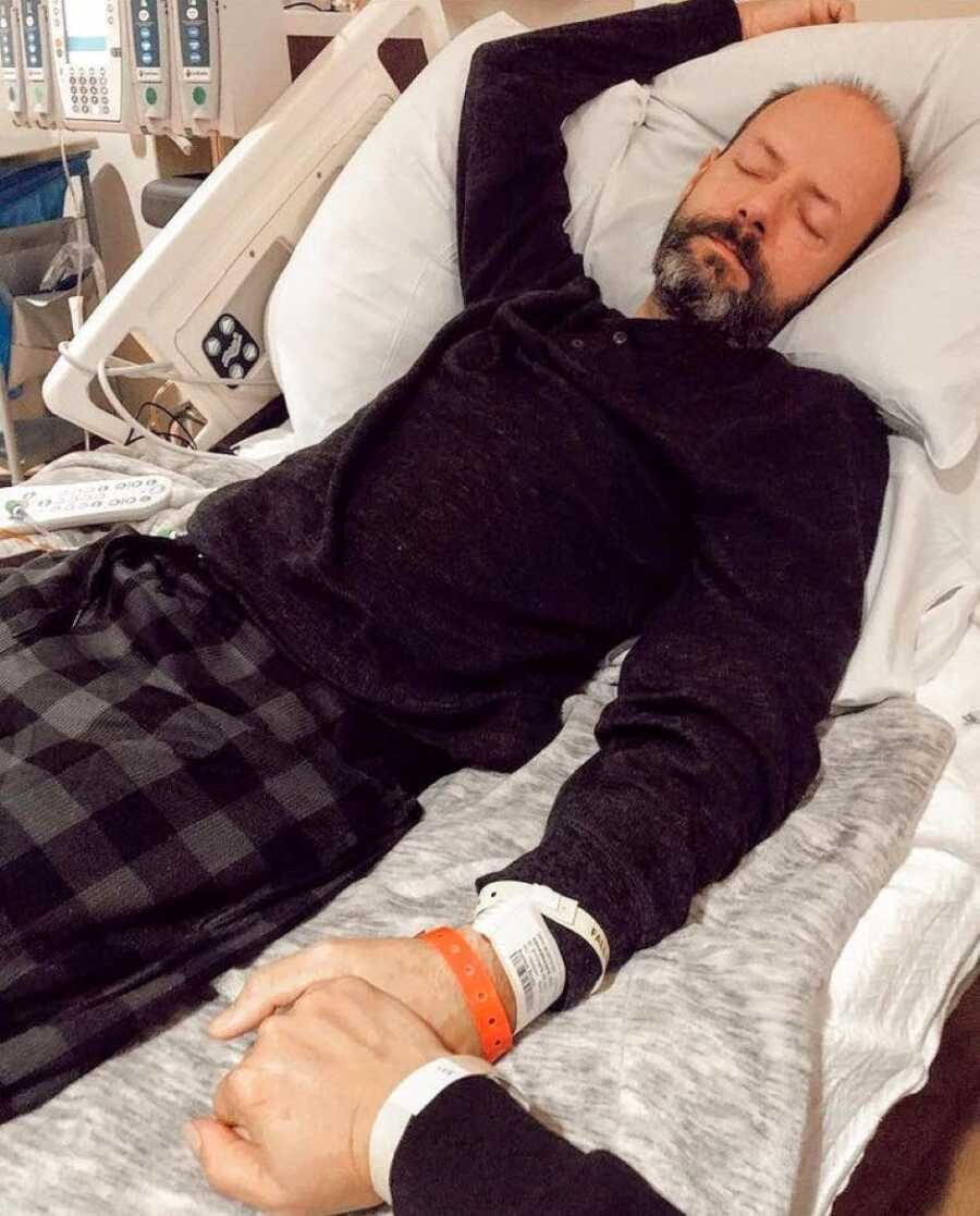 Woman holds hands with her husband dying of cancer while he lays in a hospital bed in black pajamas