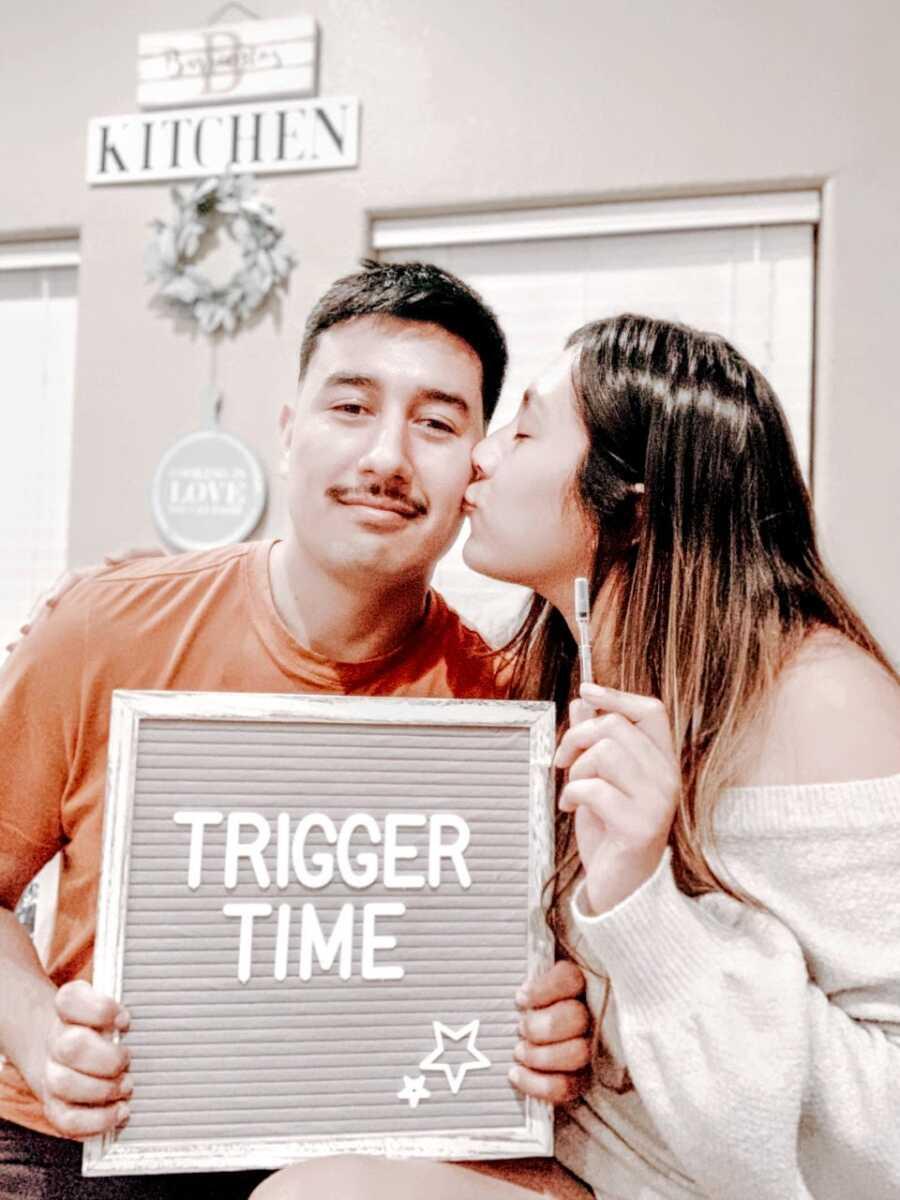 """女人亲吻她的伴侣的脸颊,而他拿着一个写着""""触发时间""""的牌子,她拿着一根试管受精的针"""