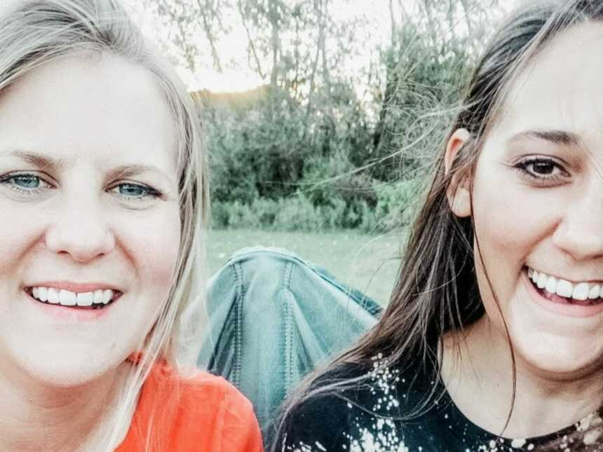 Mom and stepmom giggle together while taking selfies at one of their kids' football games