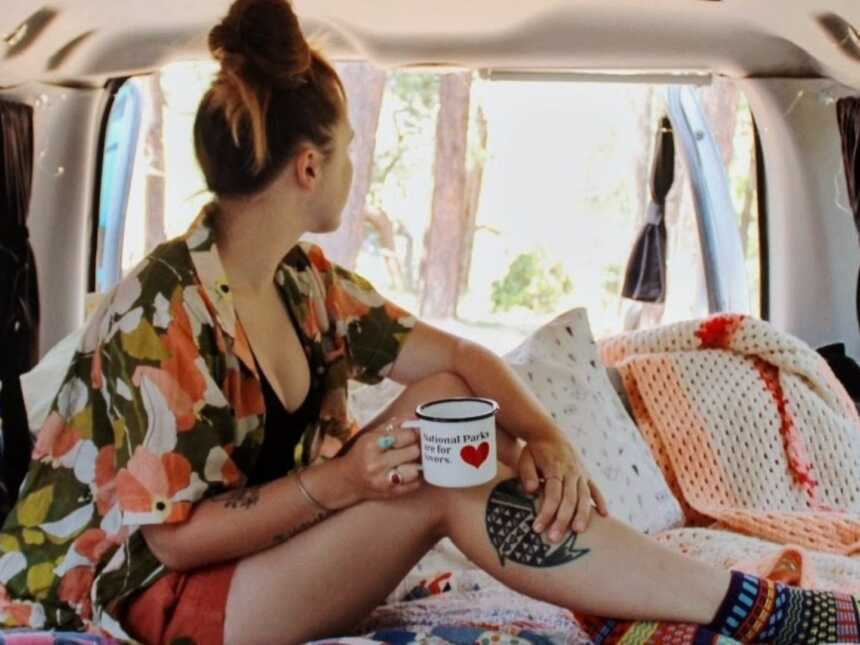 Van life traveler poses for an Instagram photo holding an empty coffee mug while sitting in the back of her van