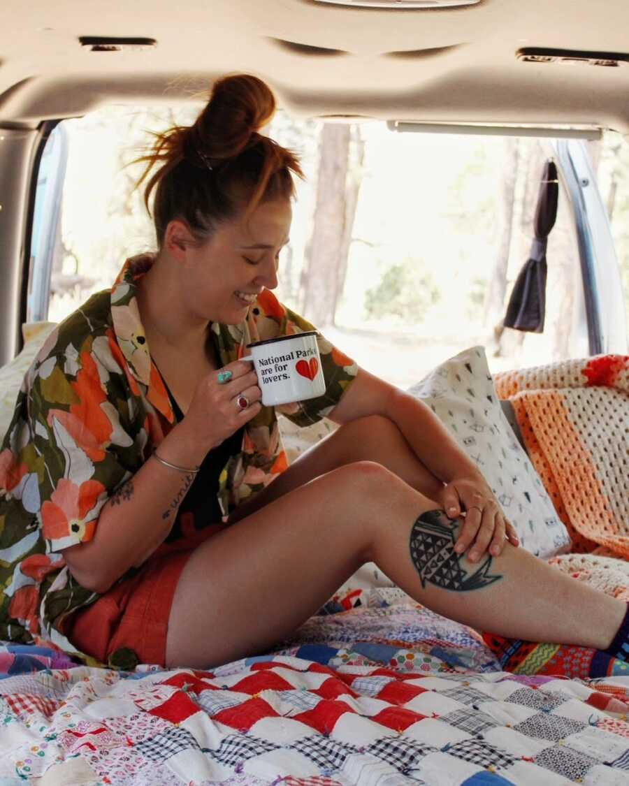 Van life traveler poses for a photo, fake laughing and holding an empty coffee cup, while sitting in the back of her van
