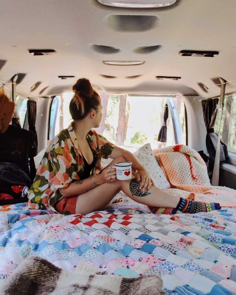 Woman looks out over the view out of the back of her van she travels in with her boyfriend
