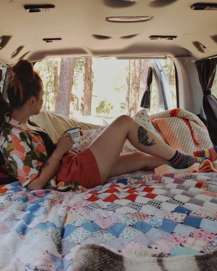 Van life traveler poses for a photo in the van she shares with her boyfriend while looking out at the trees