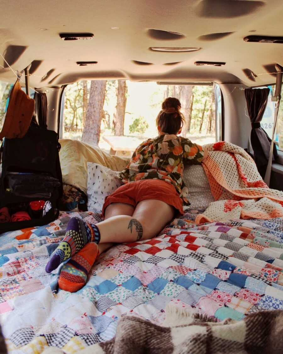 Woman lays on her stomach on a bunch of pillows while looking out of the back of her open van, taking in the view