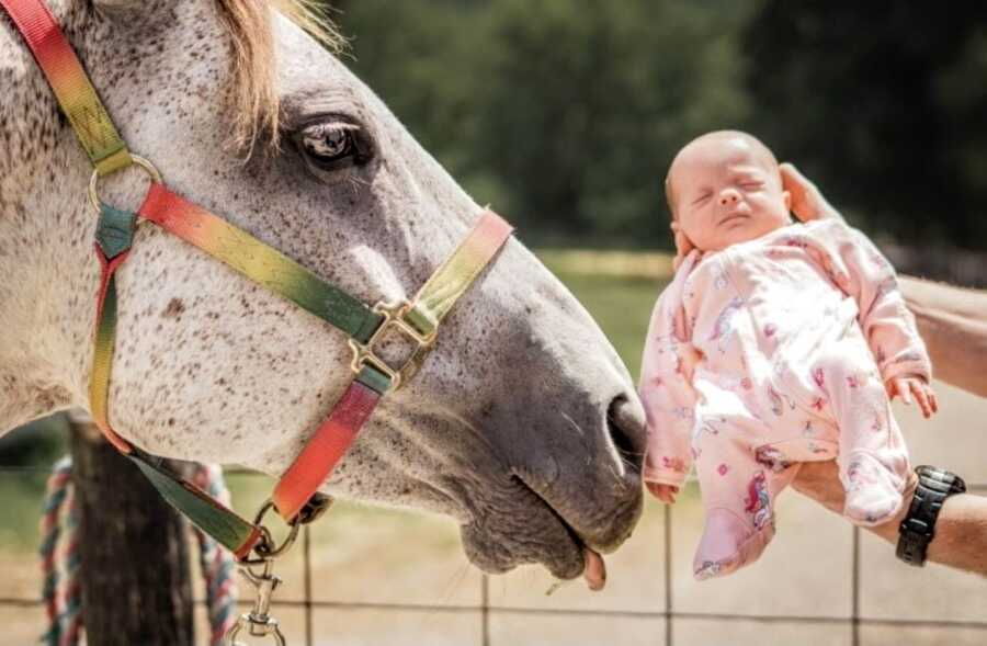 Mom holds one of her twin daughters up to a horse on her Kentucky farm