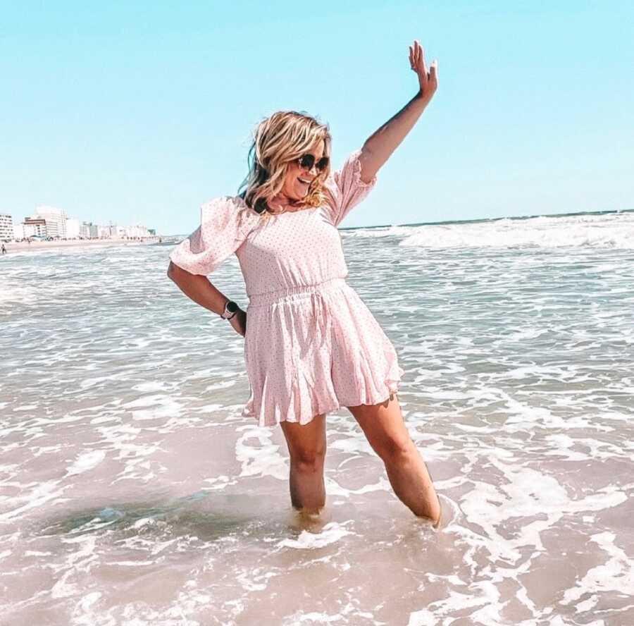 一名女子在海滩上拍照庆祝她的戒酒之旅
