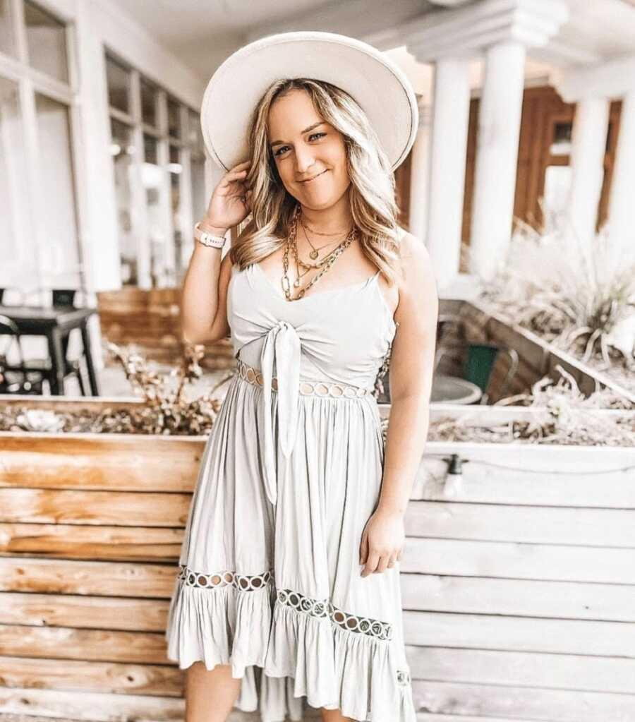 从酗酒中恢复的女人拍了一张照片,穿着漂亮的棕褐色太阳裙和配套的帽子