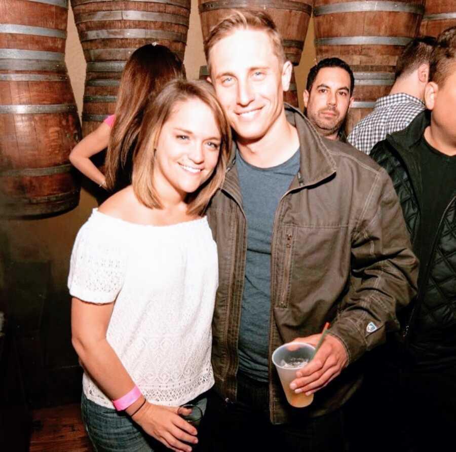 奋斗与酒精中毒的妇女用她的丈夫拍一张照片,而在与在他们后面的桶的酒吧