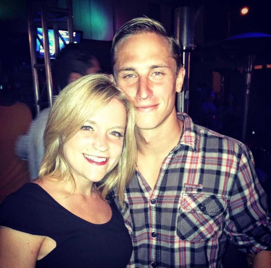年轻夫妇为照片微笑,当在夜总会时
