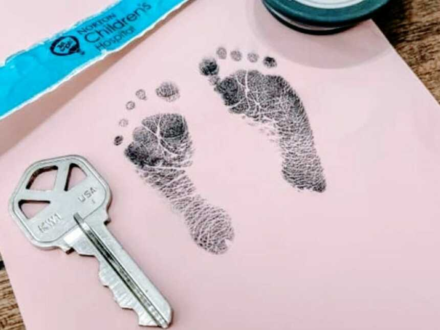 NICU mama snaps a photo of her newborn's feet stamps next to a house key